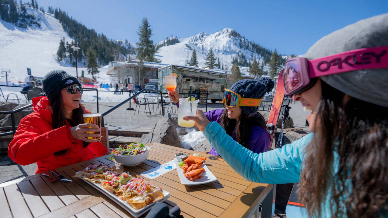 Three women sitting outdoors at Rocker at Squaw on a sunny day with the slopes in the background